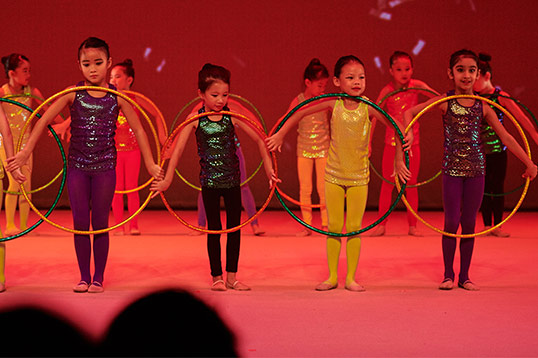 performing gymnasts with hula hoop